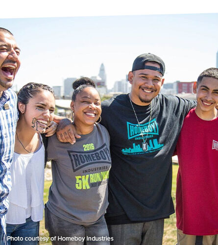 Photo: A group of people with their arms around one another. Caption: photo courtesy of Homeboy Industries.