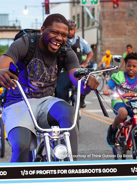Photo: A group of people smiling while riding their bikes on the side of the road. Caption: photo courtesy of Think Outside Da Block. Text on ribbon: 1/3 of profits for Grassroots Good.